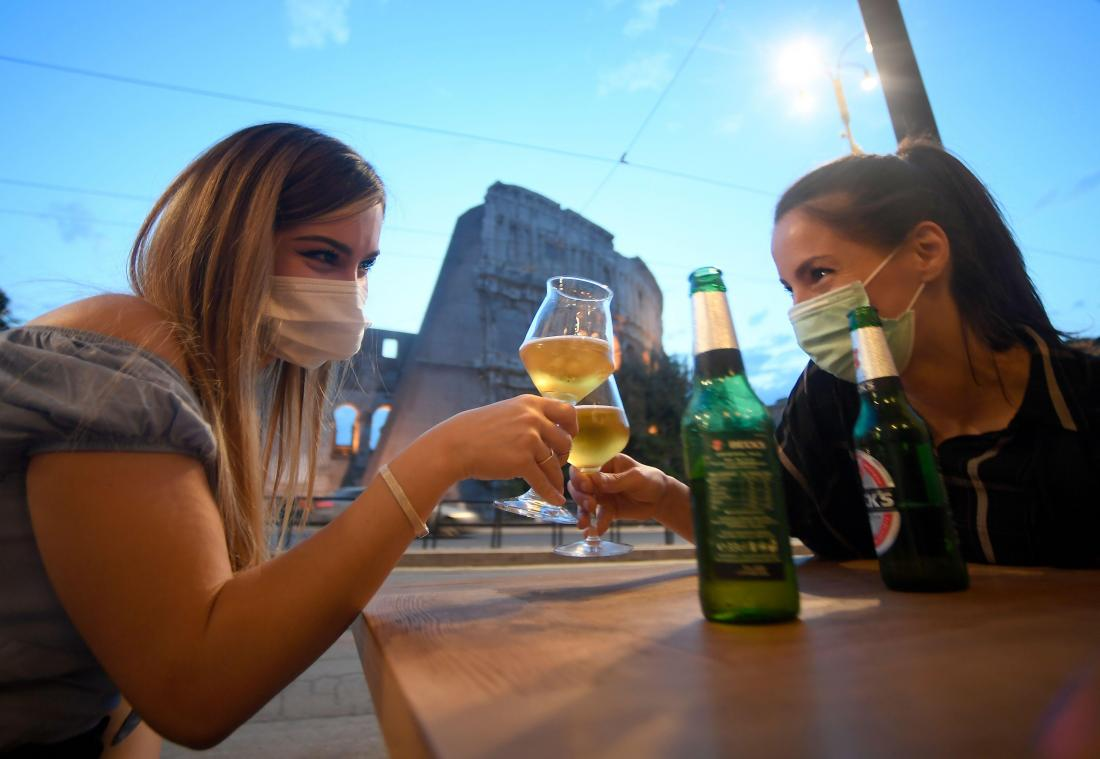 Youth gather for an aperitif drink outside a bar in the colosseum in Rome, on May 18, 2020 as the country's lockdown is easing after over two months, aimed at curbing the spread of the COVID-19 infection, caused by the novel coronavirus. - Restaurants and churches reopen in Italy on May 18, 2020 as part of a fresh wave of lockdown easing in Europe and the country's latest step in a cautious, gradual return to normality, allowing businesses and churches to reopen after a two-month lockdown. (Photo by Filippo MONTEFORTE / AFP)